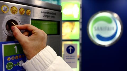 Eine Frau zahlt an einem Automat, um die Toilette an einer Raststätte zu nutzen.