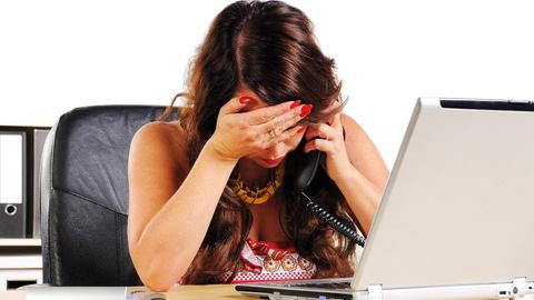 Eine Frau sitzt verärgert vor dem Rechner.