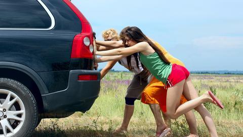 Drei Frauen schieben ein Auto an.