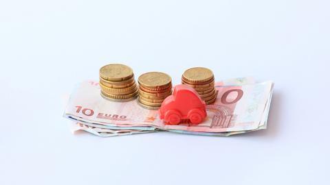 kleines Spielzeugauto auf Geldscheinen