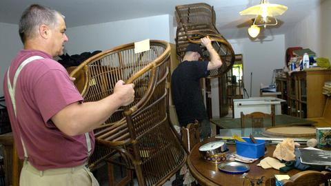 Ein Mitarbeiter einer Entrümplungsfirma schleppt einen Sessel.