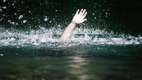 Ein Mann geht in einem See unter.