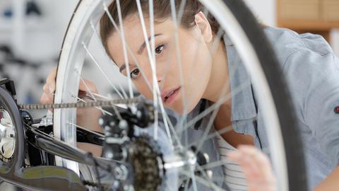 junge Frau vor fahrrad hinterrad