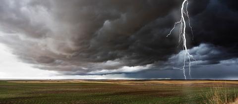 freies Feld mit dunklen Gewitterwolken und einem Blitz