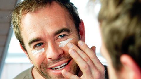 Mann bekämpft seine Augenfältchen mit Creme