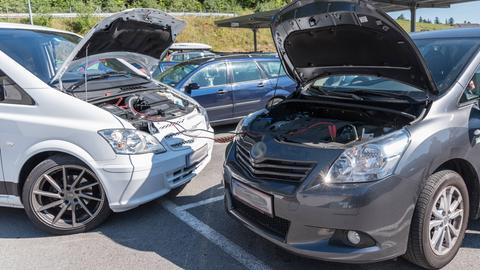 Geöffnete Motorhauben zweier Autos, die sich Starthilfe geben.
