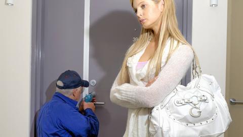 Eine vom Schlüsseldienst genervte Frau wartet darauf, dass die Tür geöffnet wird.