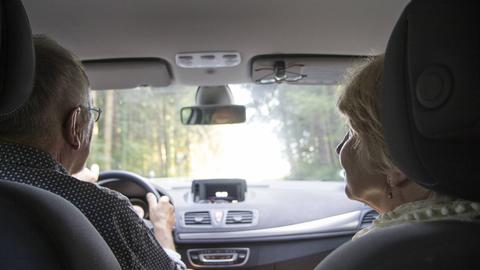 Ein Senioren-Pärchen im Auto.