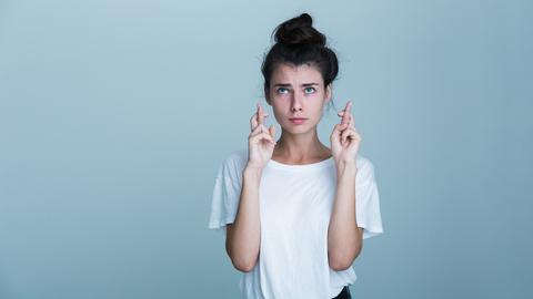 Eine junge Frau guckt nachdenklich und hält die Finger gekreuzt.