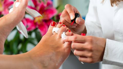 Eine Frau lässt sich die Fußnägel lackieren.
