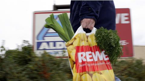 Mann mit Rewe-Einkaufstasche vor einem Aldi