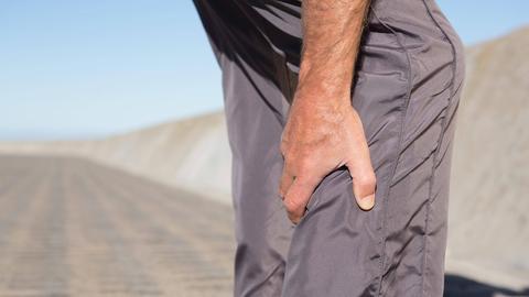 Ein Mann hält sich das Bein.