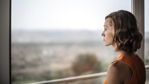 traurige Frau schaut aus dem Fenster