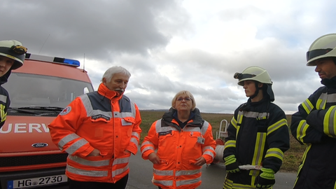 Ein Mann und eine Frau in neonorangener Rettungsjacke und zwei Feuerwehrleute vor einem Feuerwehrauto am Feld.