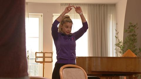 Eine junge blonde Frau mit Haarzopf in lila Trainingsjacke hebt die Hände Richtung Decke.