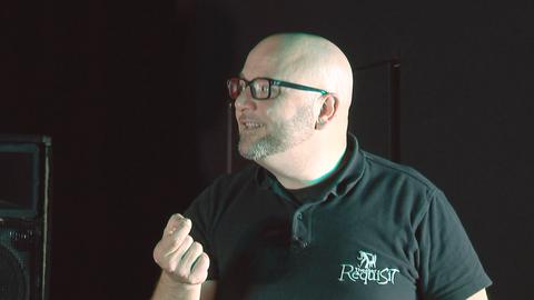Mann mit Glatze und Brille schaut zum linken Bildrand.