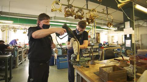 Zwei Metallblasinstrumentenmacher in der Werkstatt bei der Arbeit.