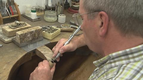 Goldschmied Dieter Hainmüller bei der Arbeit mit einem Ring an seine Schmiedetisch.