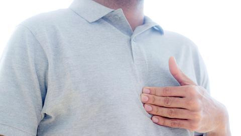 Ein Mann fasst sich an die Brust