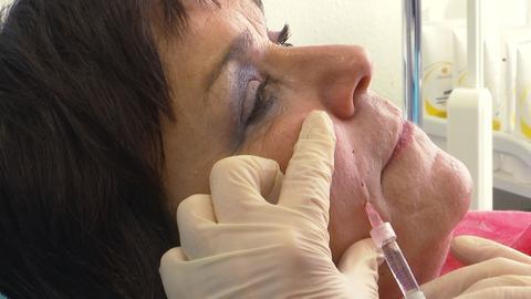 Patientin Karin Volk bekommt Hyaluron ins Gesicht gespritzt.