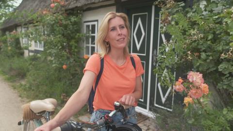 Eine junge Frau schiebt ihr Fahrrad
