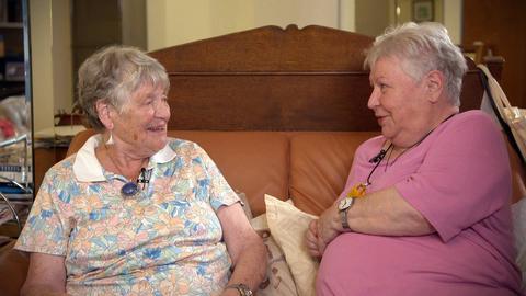 Zwei ältere Frauen sitzen auf einem Bett und schauen sich lächeln an.
