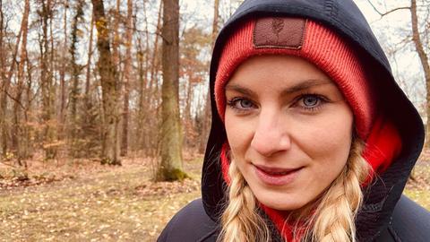 Ratgeber-Reporterin Maike Tschorn mit Kapuzenjacke im Wald.