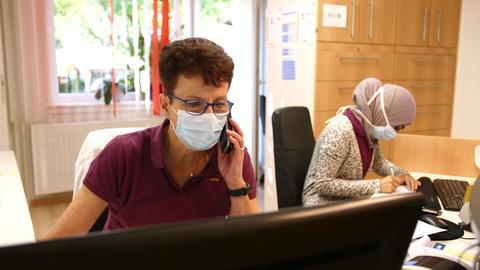 Die Sprechstundenhilfe in Dr. Siehs Praxis sitzt an der Theke, schaut auf ihren Computerbildschirm und telefoniert währenddessen.