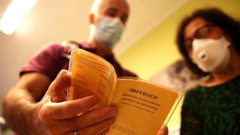 Dr. Sieh schaut mit einer Patientin in einen aufgeschlagenen Impfpass.