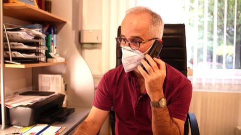 Dr. Sieh sitzt an seinem Schreibtisch und telefoniert. Er trägt dabei eine Mund-Nasen-Maske.