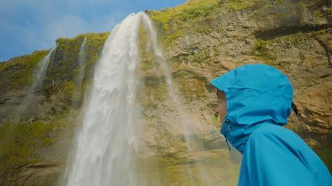 Nina Heins schaut hoch zu einem Wasserfall.