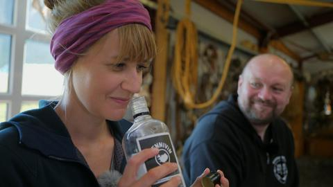 Nina Heins riecht an einer offenen Flasche Gammelhai-Schnaps.