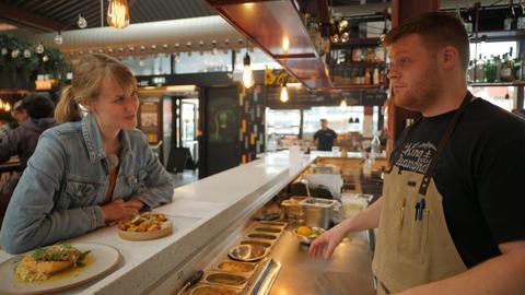 """Nina Heins sitzt am Tresen einer Food Bar und lächelt den """"Barkeeper"""" an."""