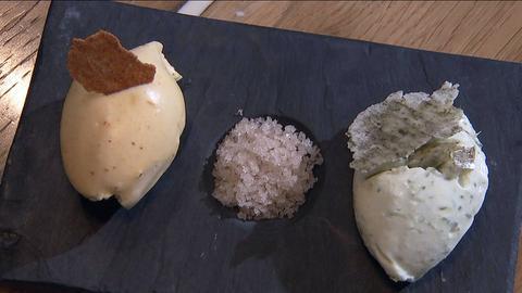 Mousse-Dessert angerichtet auf einer Schiefernplatte mit grobem Salz in der Mitte.