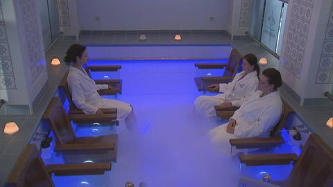 Drei Frauen im Bademantel sitzen in einem blau beleuchteten Pool.
