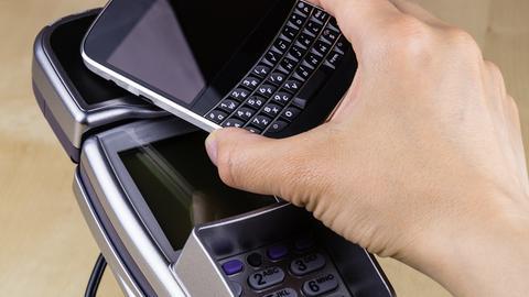 Ein Smartphone wird über ein Kartenlesegerät gehalten.