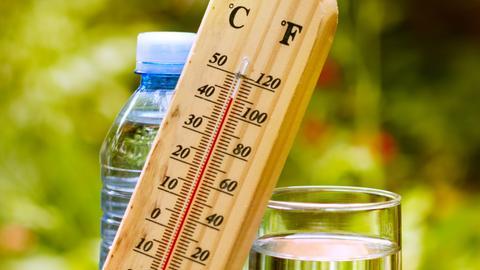 Ein Thermometer aus Holz an ein Wasserglas gelehnt. Anzeige: fast 40 Grad Celsius.
