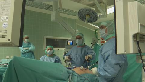 Mehrere Ärzte und Ärztinnen in grünen Kitteln im OP.