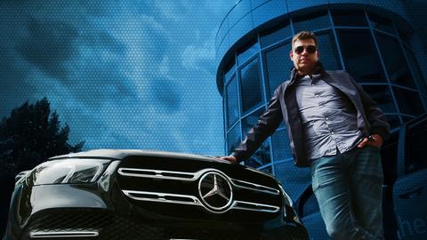Philipp Engel steht posend und protzend mit Sonnenbrille vor einem Mercedes-SUV und hat die Hand auf die Motorhaube gelegt.