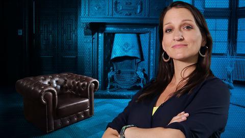 Julia Tzschätzsch mit verschränkten Armen, im Hintergrund, blau eingefärbt, ein herrschaftlicher Salon.