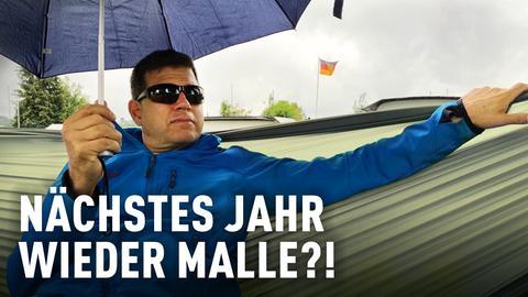 Philipp Engel sitzt mit Regenschirm in einer Hängematte auf einem deutschen Campingplatz.
