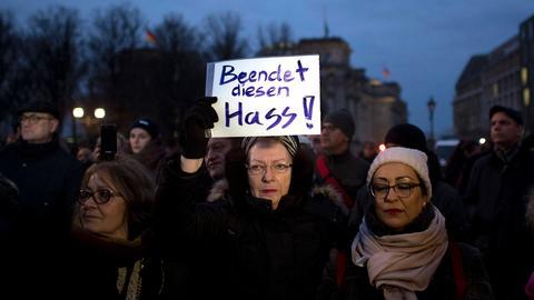 """Eine Frau hält ein Plakt hoch mit der Aufschrift """"Beendet diesen Hass"""""""