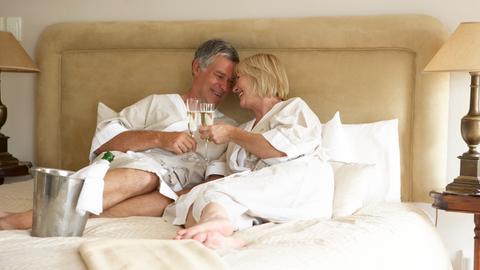 Älteres Liebespaar im Bett mit Sekt.