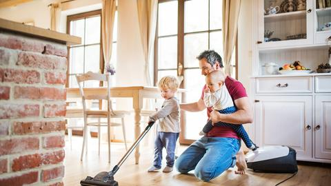 Ein Vater mit seinen Kindern beim Staubsaugen
