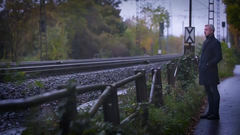 Ein Mann steht an einem Gleis