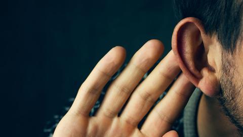 Man hält Hand ans Ohr