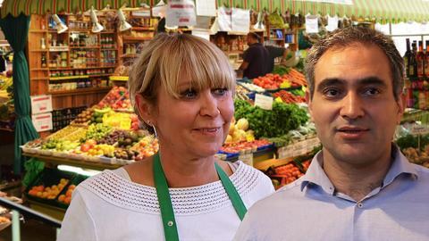 Gemüseverkäuferin und Mann im Hemd vor bunten Ständen der Frankfurter Kleinmarkthalle.