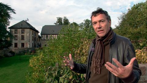 Protagonistin bohrt von außen an einem Fenster des Schlosses von Homberg.
