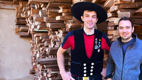 Die zwei Protagonisten stehen vor einem Haufen Holz.