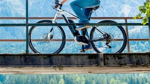 Ein Radfahrer fährt mit seinem E-Bike über eine Brücke.